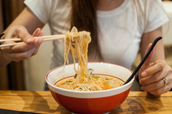 woman eating a bowl of ramen