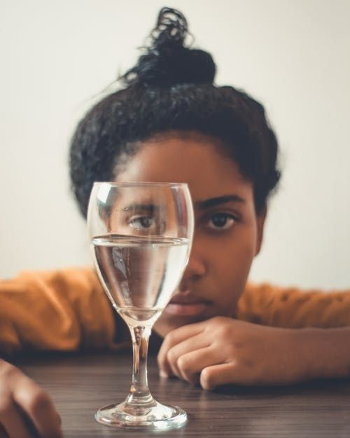 A woman looking at a glass of water
