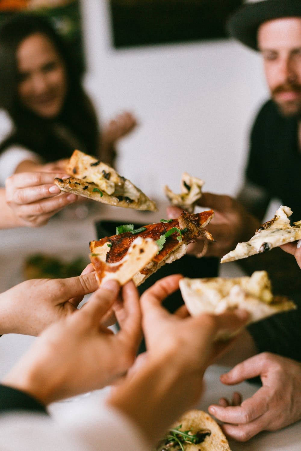 Group of friends sharing slices of pizza