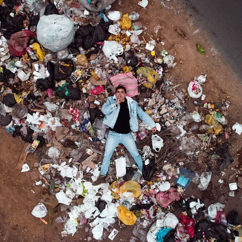 Man in Peru lays on a mountain of plastic in a landfill