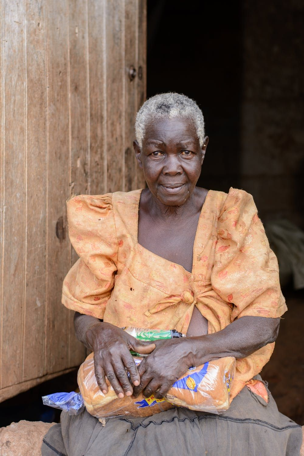 An elderly African woman in an orange shirt