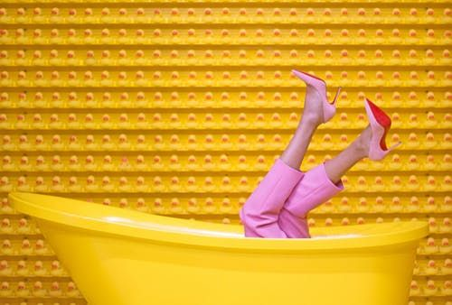 A woman with high heels in a yellow bathtub