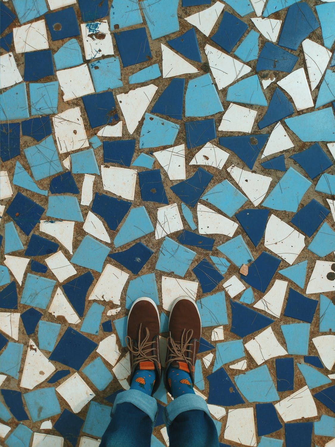 Two feet stepping on a blue and white mosaic