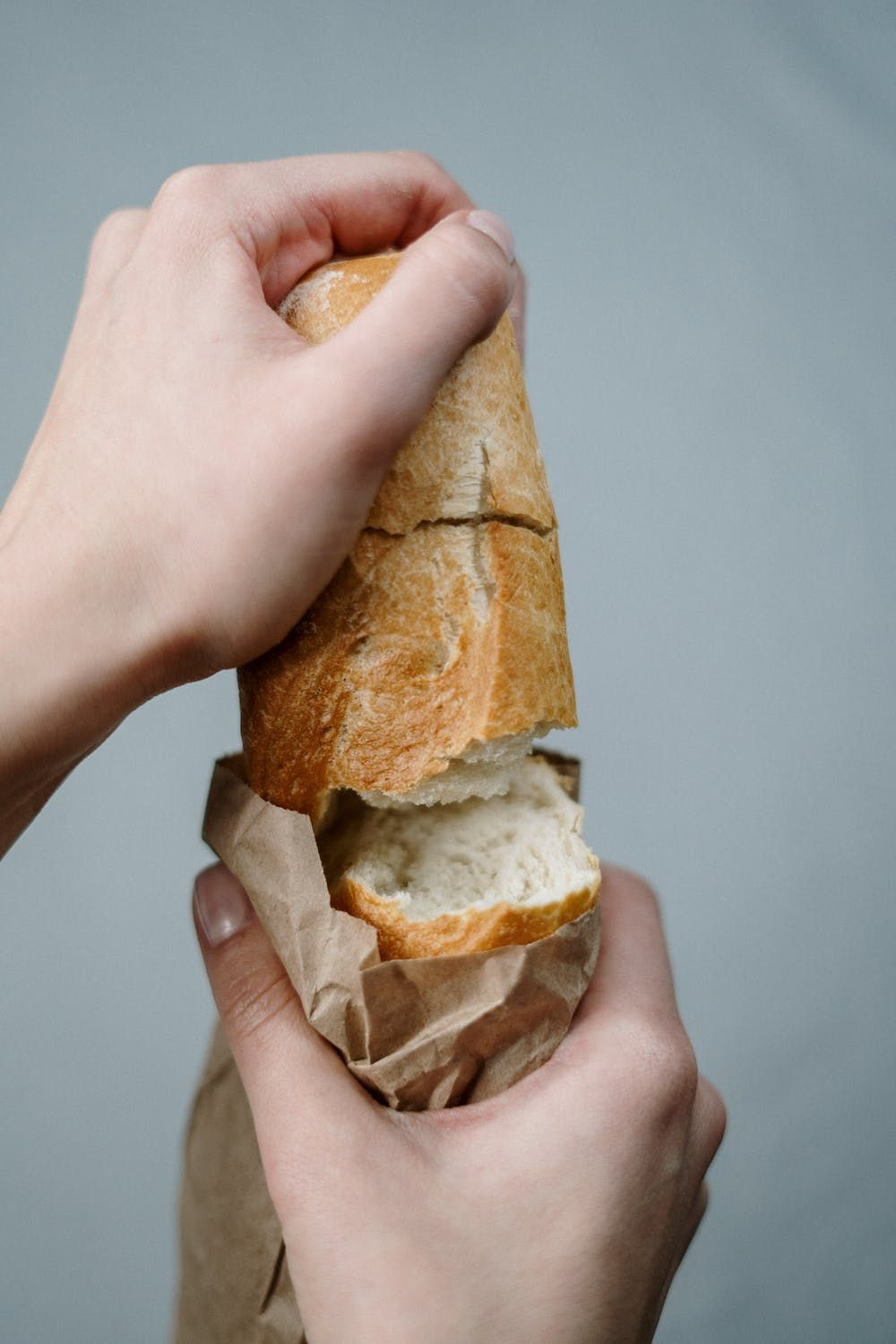 A person tearing apart a fresh loaf of bread