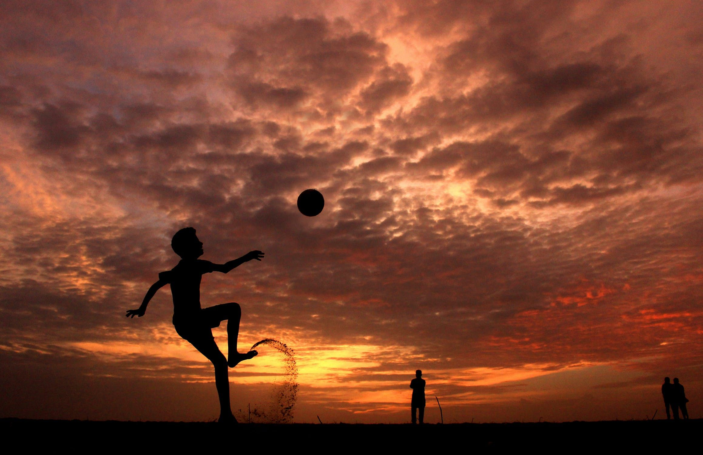 A young boy playing around with a ball under the sunset