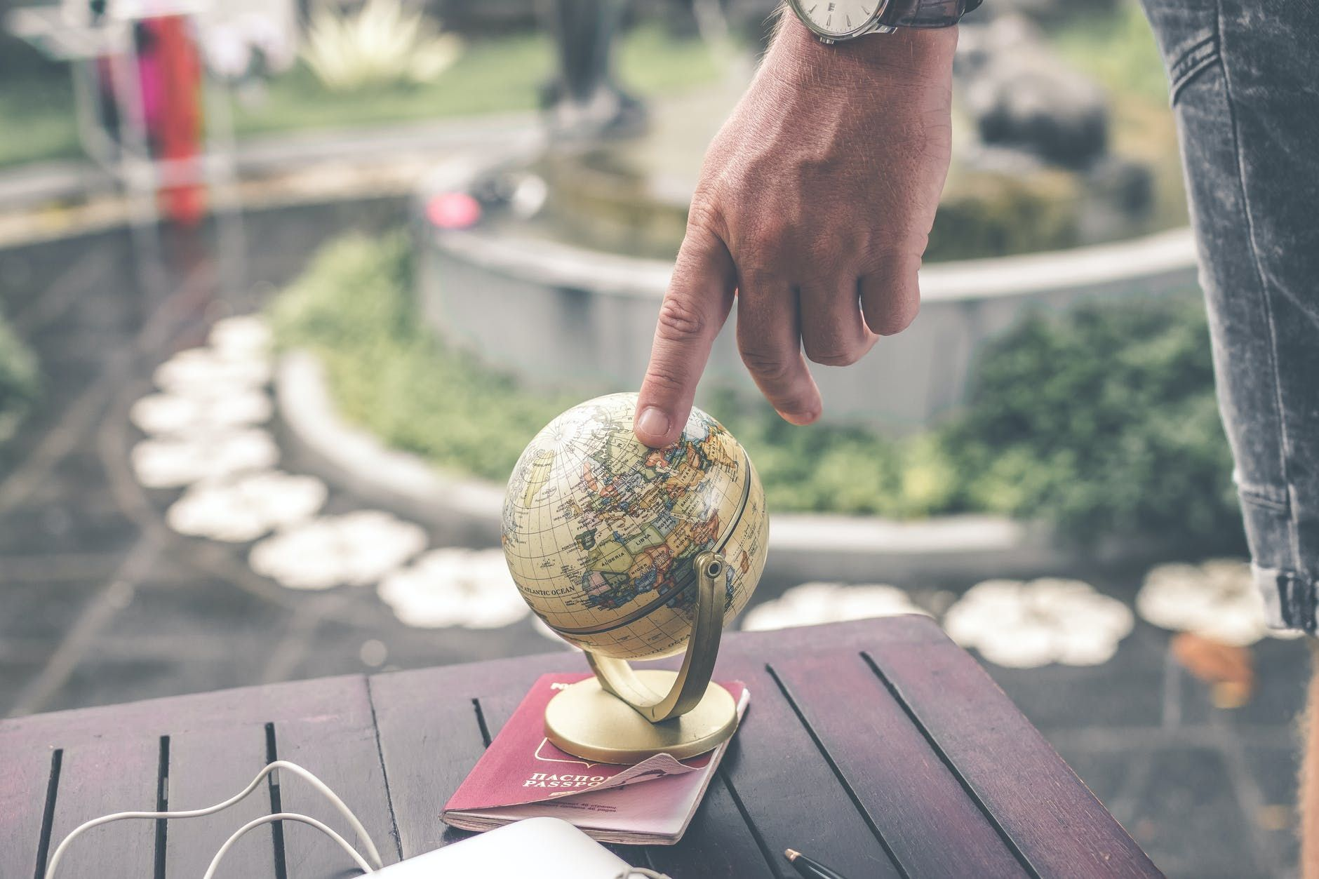 A person putting their finger on a globe of the world