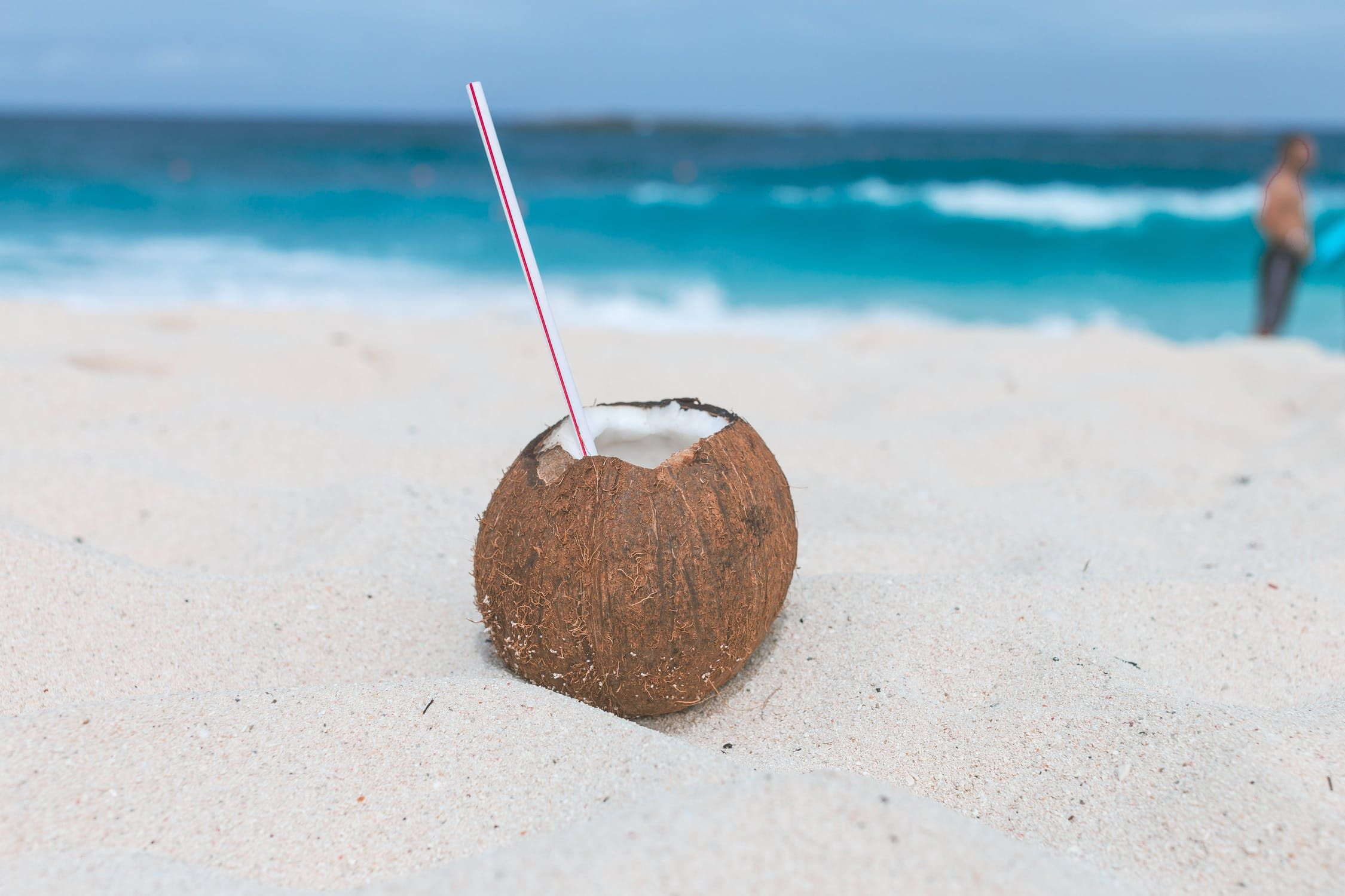 A brown coconut with a straw on the beach