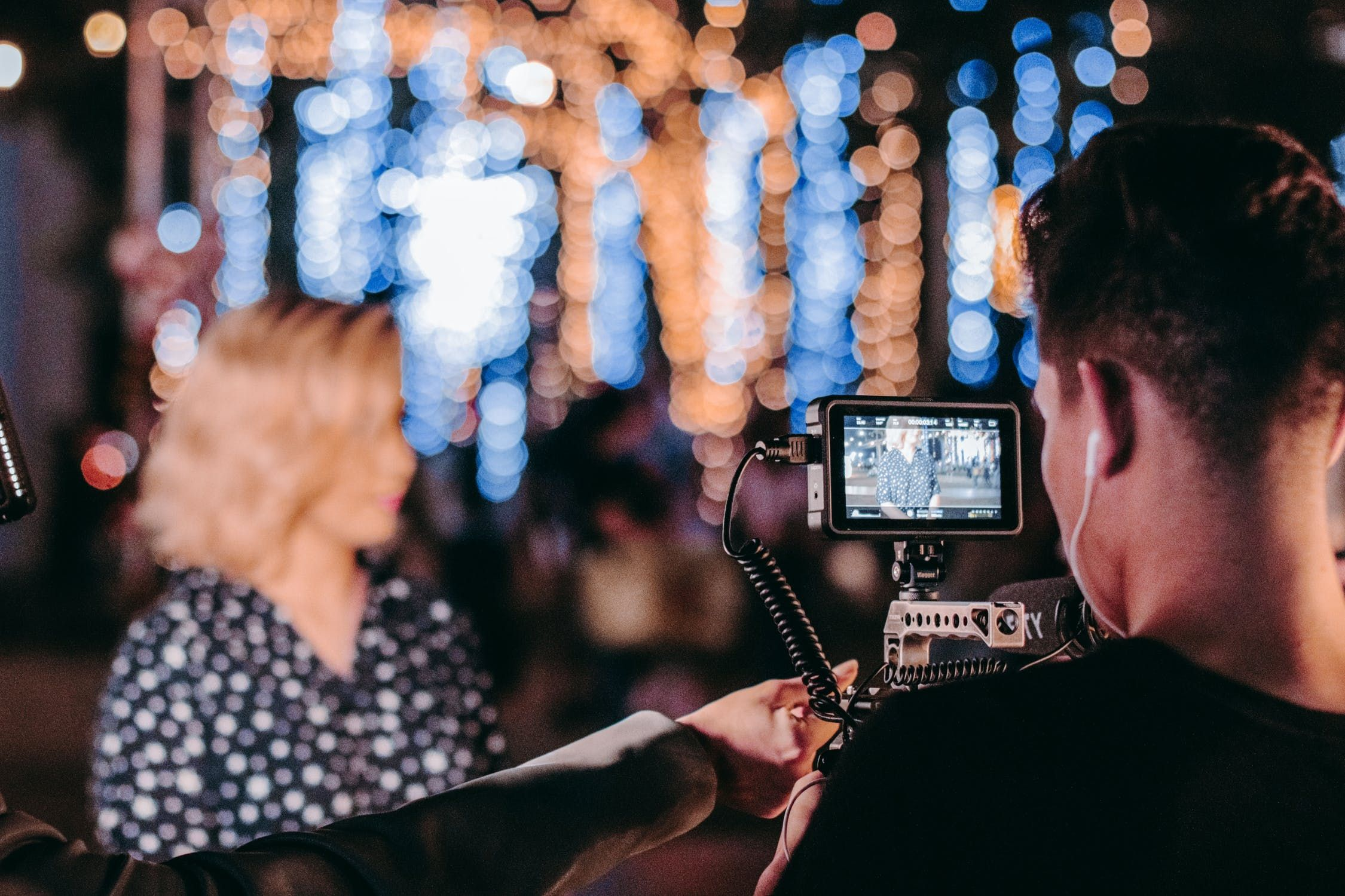 A blonde woman being filmed by a professional at a club