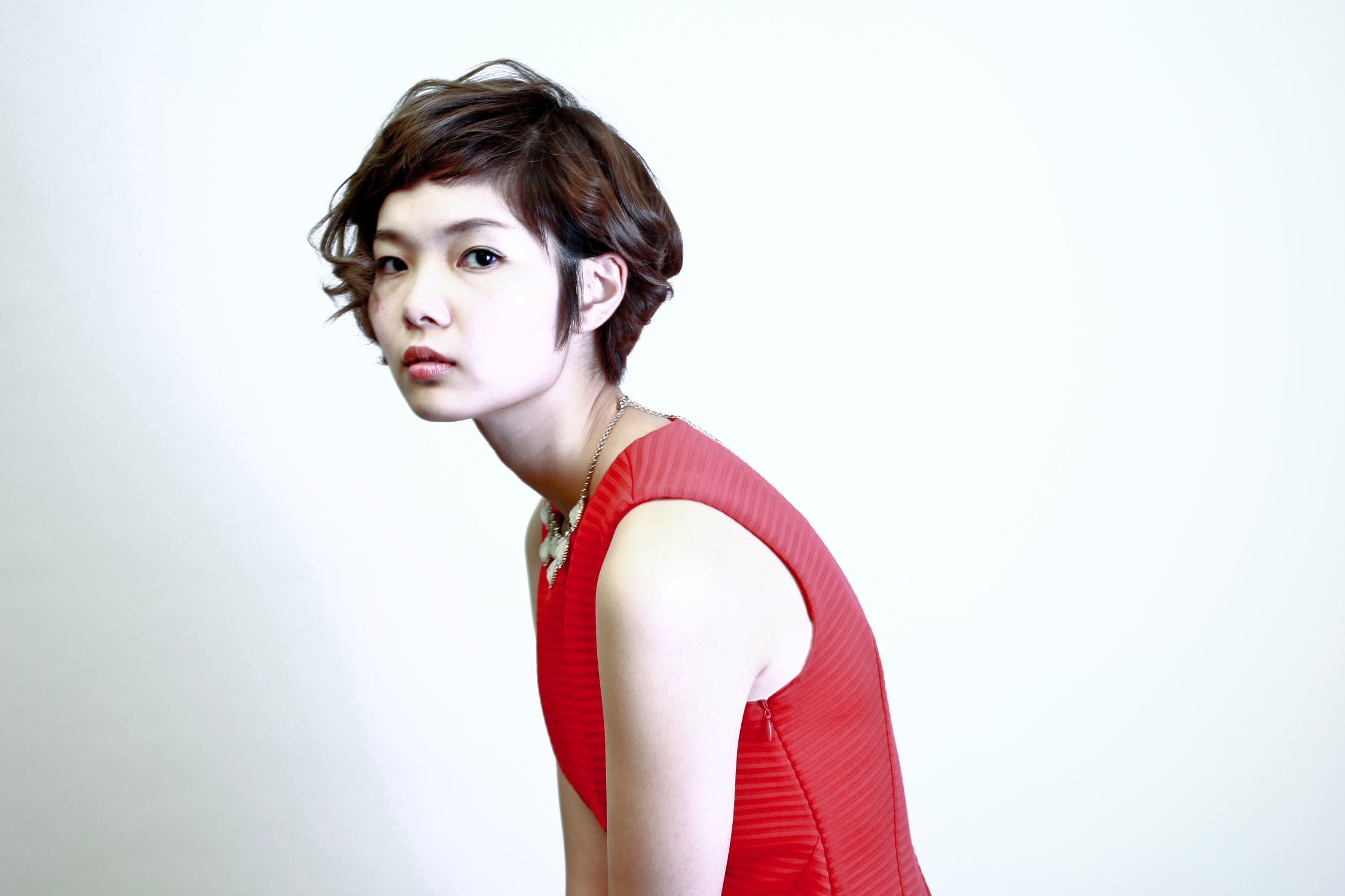 An Asian model with short hair wearing a red dress