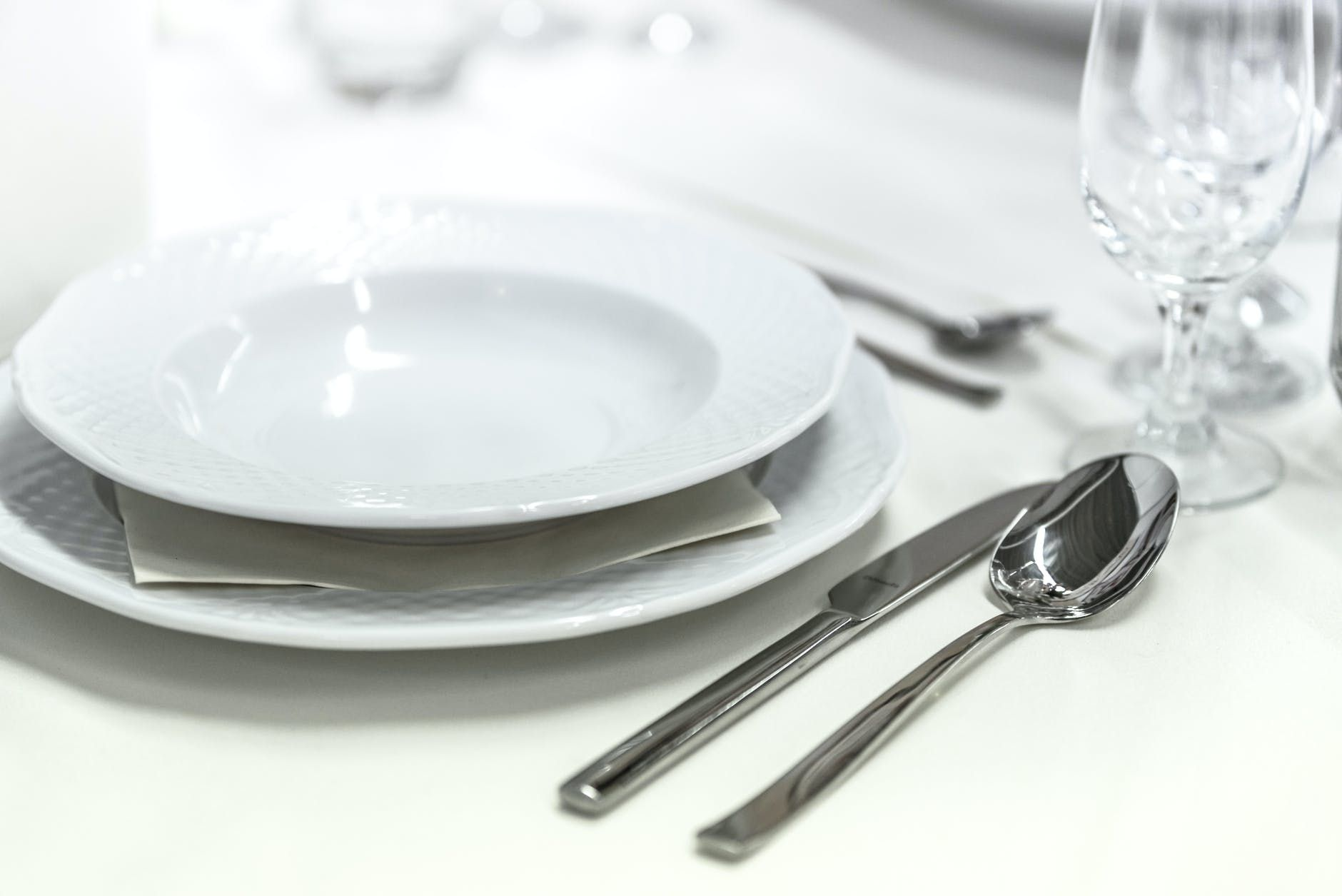 A white plate and cutlery on a table