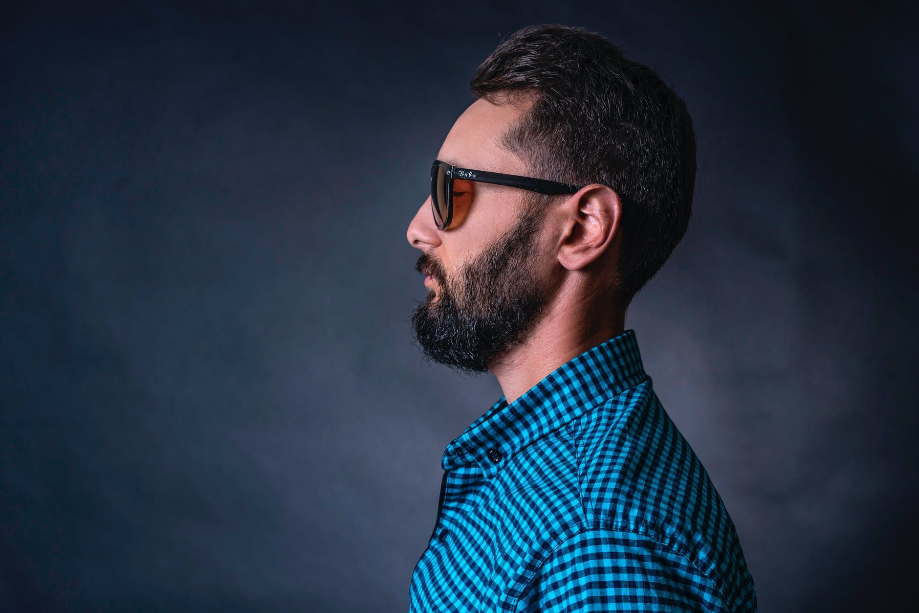A man wearing a checkered shirt and sunglasses