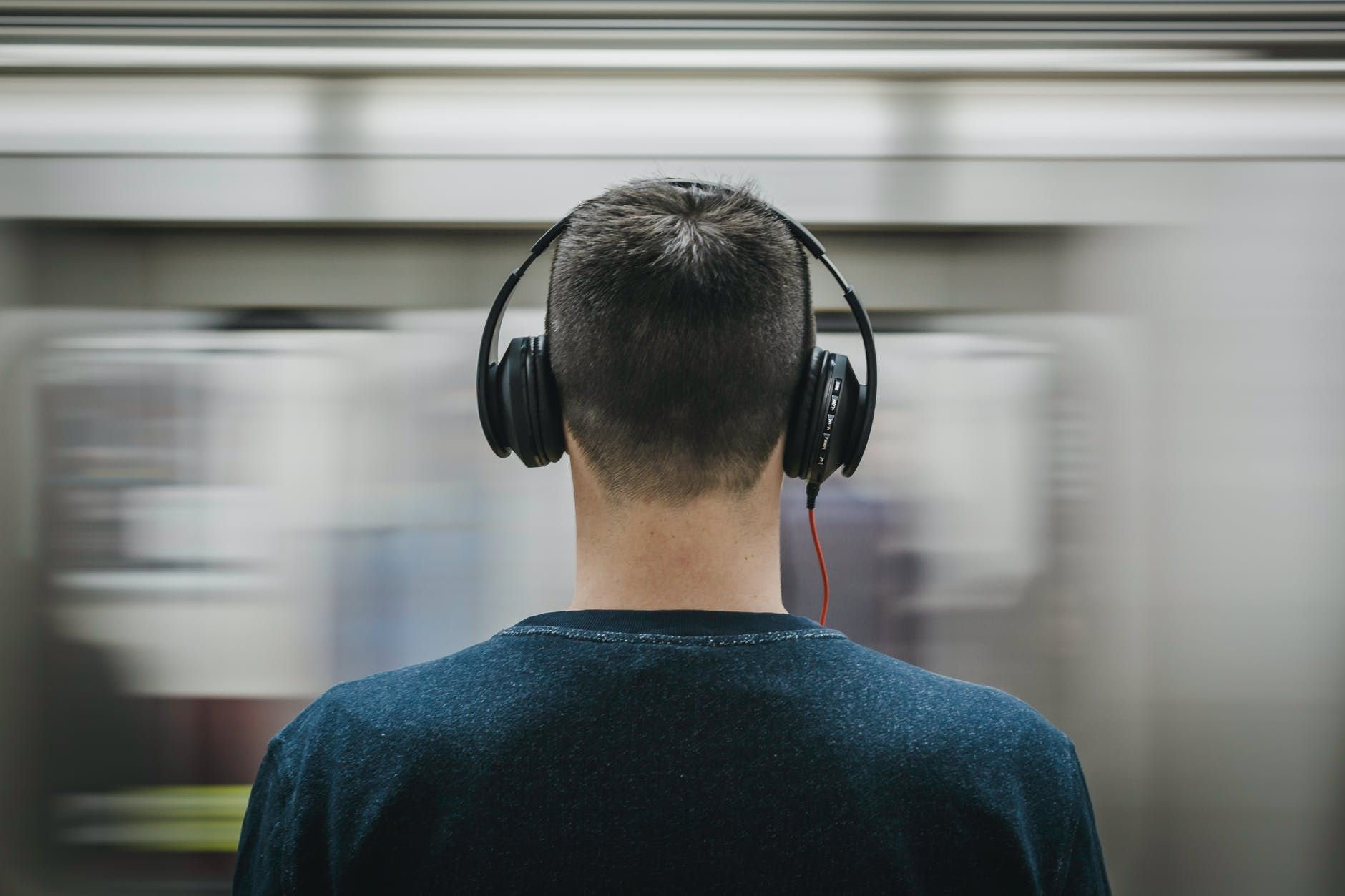 A man wearing headphones and looking out to the subway