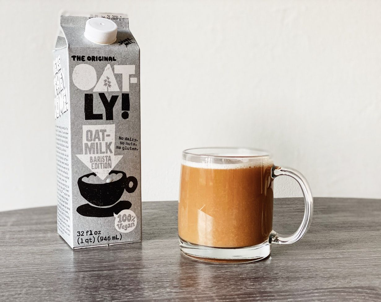 Plant-based milk brand Oatly next to a cup of coffee in a glass mug
