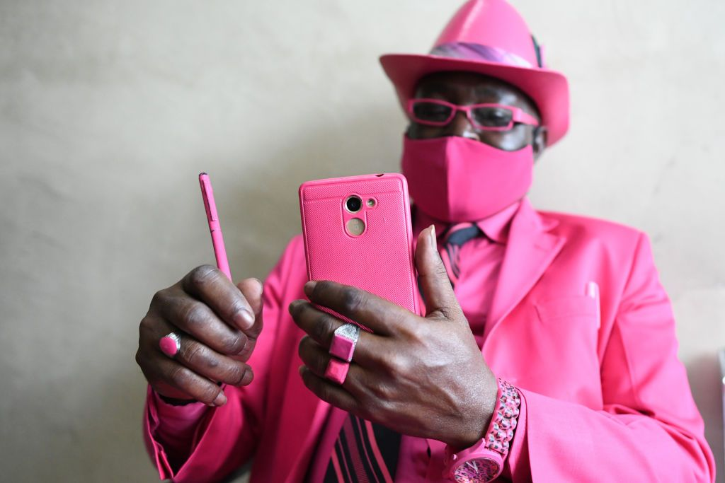 Kenyan fashionista James Mwangi Maina uses his mobile phone as he displays his suits matching his attire and accessories