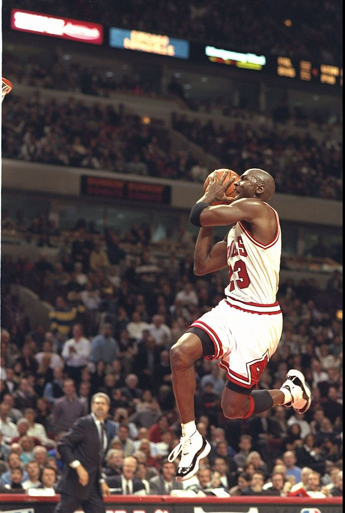Guard Michael Jordan #23 of the Chicago Bulls takes to the air in his famous moves to slam dunk against the Charlotte Hornets at the United Center