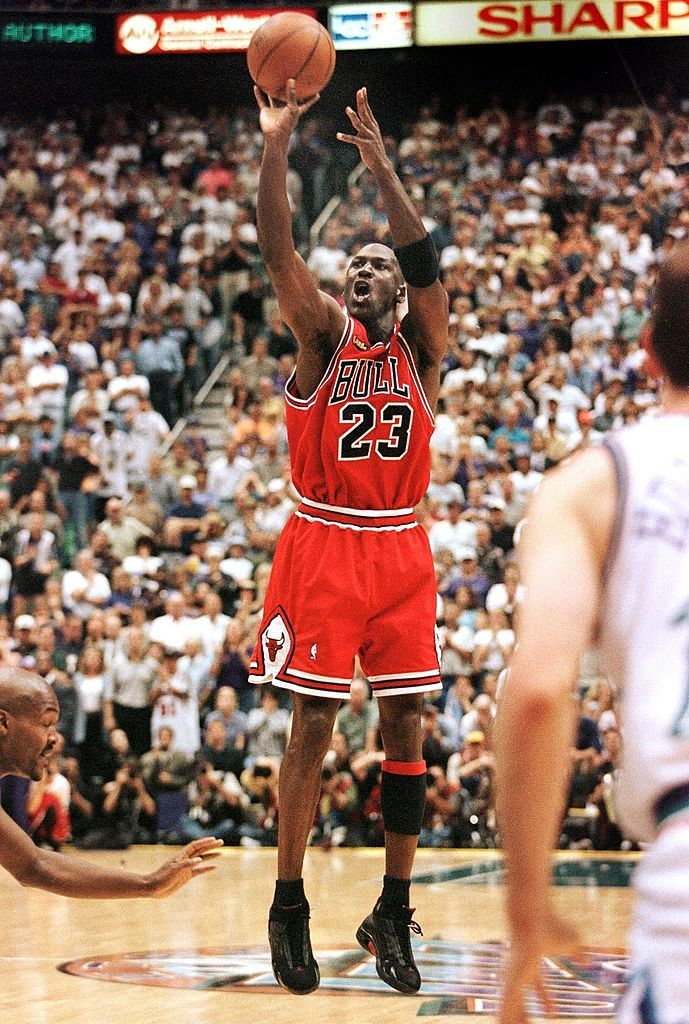 In this 14 June 1998 file photo, with 5.2 seconds left in the game, Michael Jordan of the Chicago Bulls (C) aims and shoots the game-winning jump shot