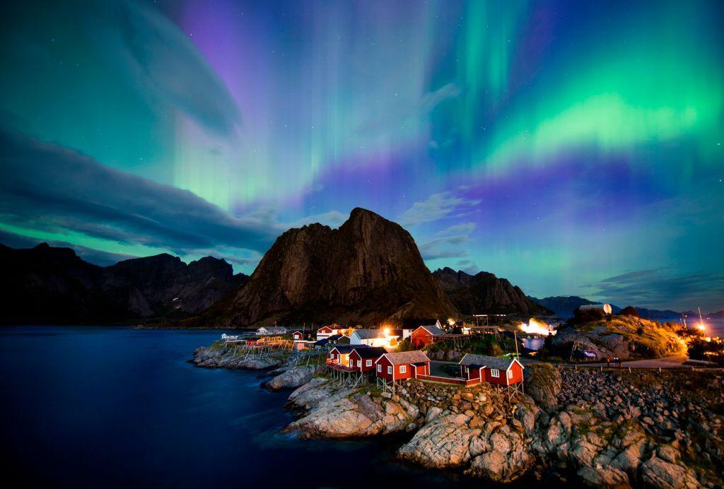 Northern lights (aurora borealis) illuminate the sky over Reinfjorden in Reine, on Lofoten Islands, Arctic Circle