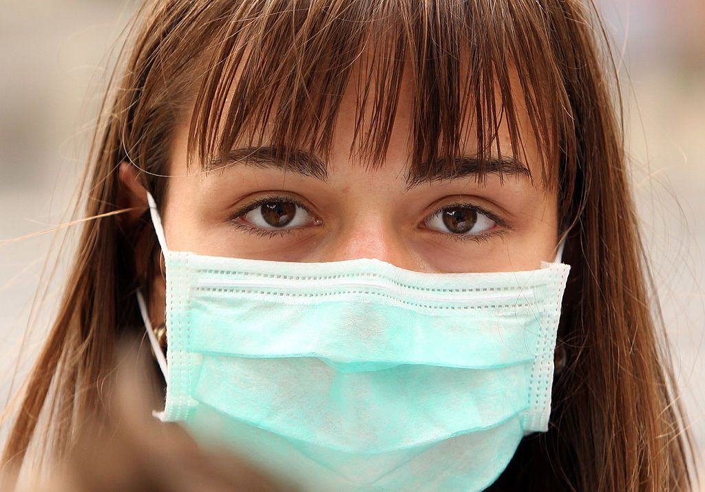 A woman wearing a surgical mask to prevent the transmission of airborne infection walks in Westminster on July 30, 2009 in London, England