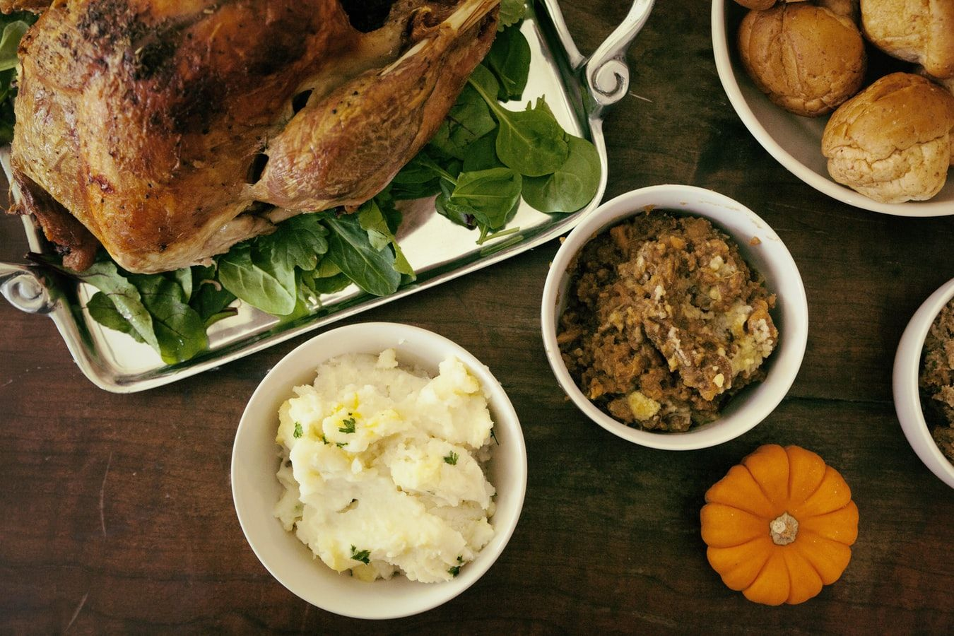 Full cooked turkey on a bed of spinach leaves surrounded by side dishes like mashed potatoes and stuffing and bread rolls and a pumpkin