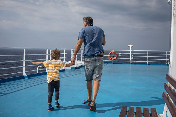 Father and son holding hands on a ship