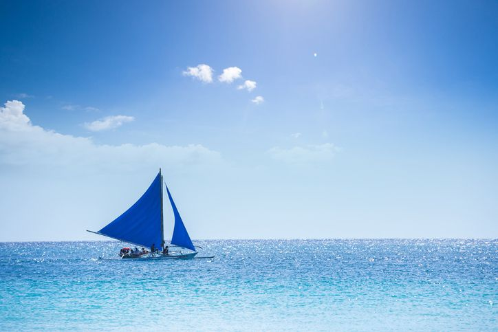Boat with blue sail in the sea
