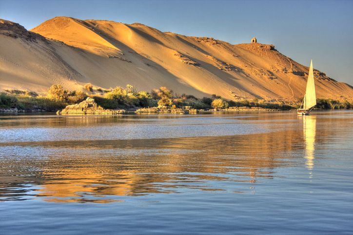 Nile river flowing through desert dunes