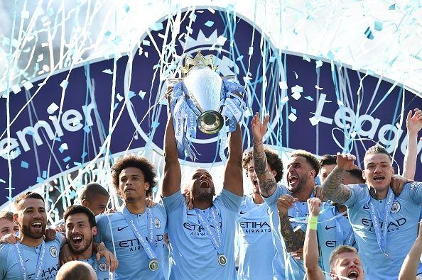 manchester city holding premier league trophy