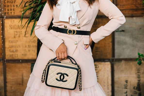 Woman in pink dress holding dior bag