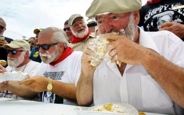 bearded men eating pies in a pie eating contest