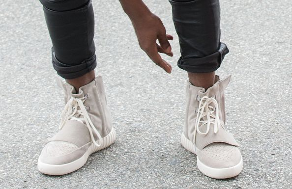Kanye west crouching with the yeezy 3 sneakers: 'yeezy 750 boost'