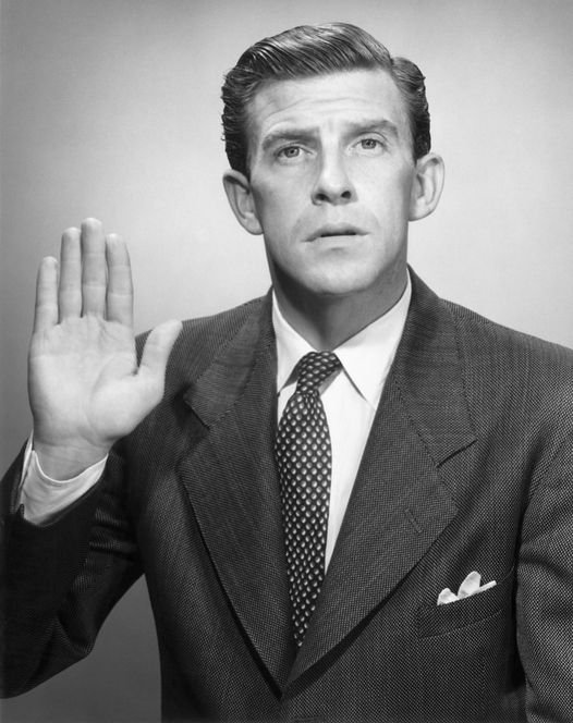 Man taking oath with his hand raised in black and white