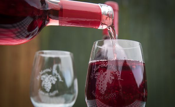 Red wine being poured into a glass cup