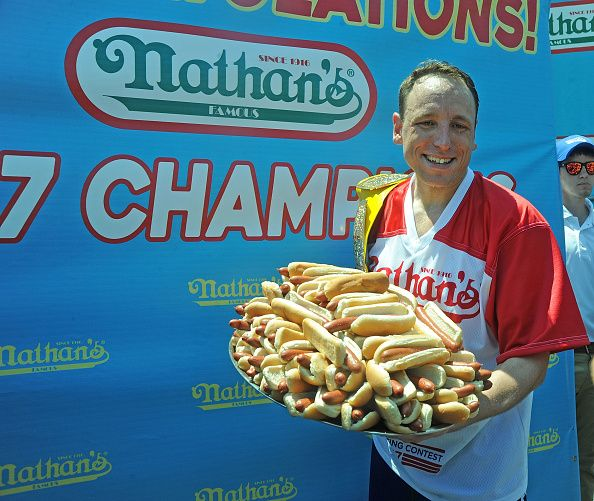 man holding tray of dozens of hot dogs