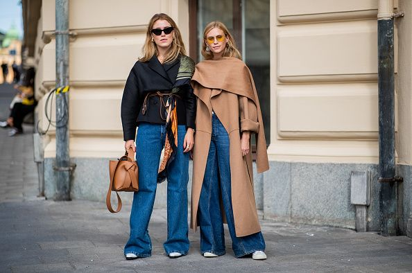 Two women posinmg in the street with blue jeans oand other random itesm of clothing