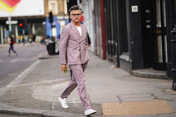 Man walking in thje street with pink suit and white sneakers