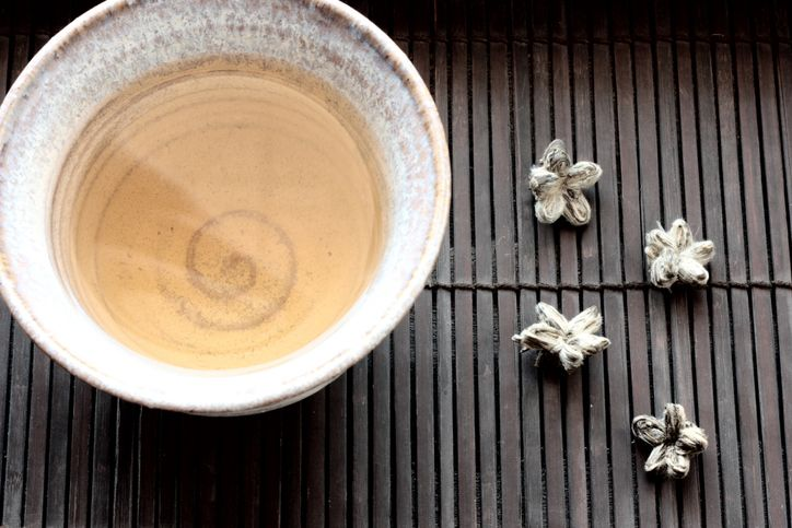 white tea on cup with white flowers beside it