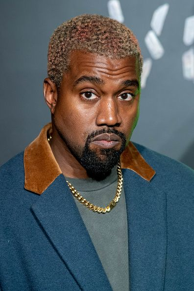 Kanye west making a face as he poess for cam,era in versace award cewremony