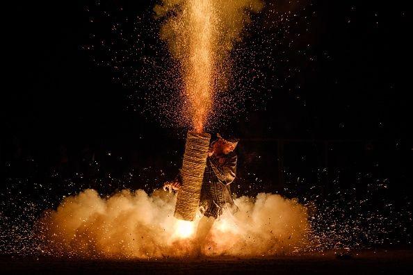 man holding gigantic bamboo firework