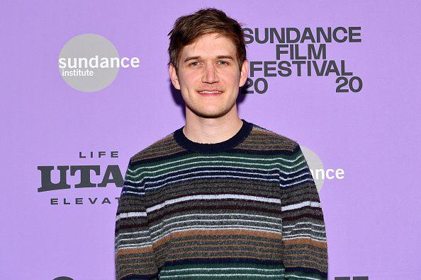 Bo Burnham standing in front of purple background