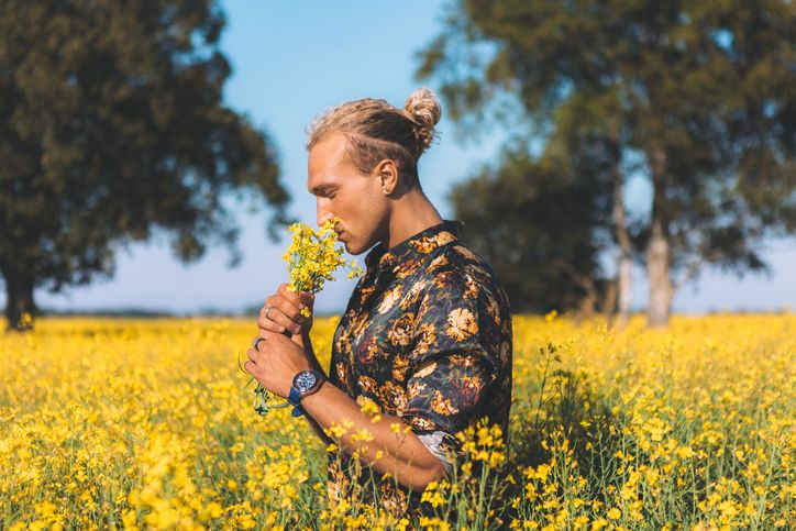 blonde haired man smells flowers in field