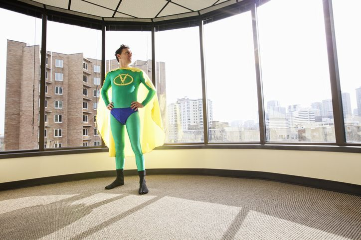 man dressed as superhero standing by the window of his office