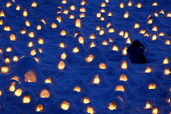 Tiny little candle-lit snow huts on the river bank
