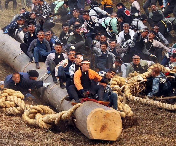 japanese peoplkle riding huge log down a mountain