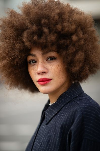 woman with curly hjair and suit